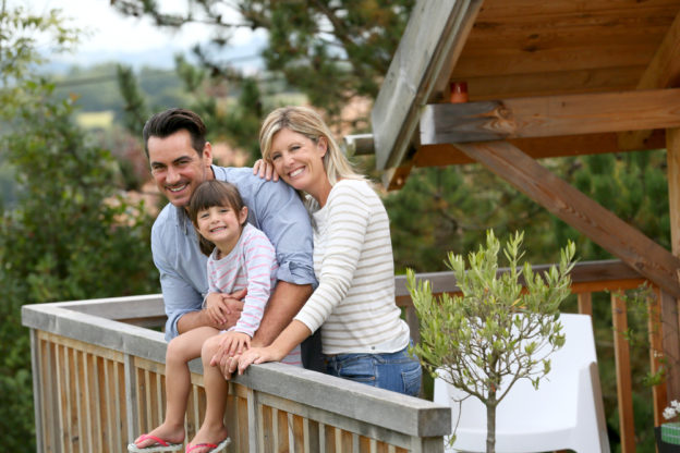 Happy family on the deck of their cabin.