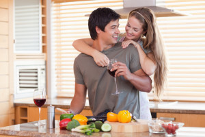 Young couple drinking wine, cooking, and embracing in their Pigeon Fore cabin's kitchen